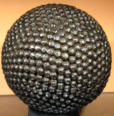 """Grâce aux clous les boules furent plus lourdes et leurs diamètres augmentaient (100 à 150 mm et le poids aussi jusque 1500 Gr), en particulier pour les boules du jeu """"à la lyonnaise"""". Plus tard on employait des clous à tête plate. A partir de là les fabricants furent de vrais artistes, les clous étaient en différentes matières et couleurs (fer, cuivre, laiton) ce qui permettait de faire plusieurs sorte de symboles, le plus souvent des chiffres ou des initiales mais aussi des étoiles et autres sujets d'après les souhaits des joueurs (en quelque sorte """"les armoiries"""" du bouliste). Par la suite (vers 1900) on a fabriqué des boules de diamètre 70 à 90 mm, c'étaient les premières boules pour le jeu provençal et plus tard pour la pétanque. La boule ci-dessous, plus récente est recouverte de clous faits mécaniquement."""